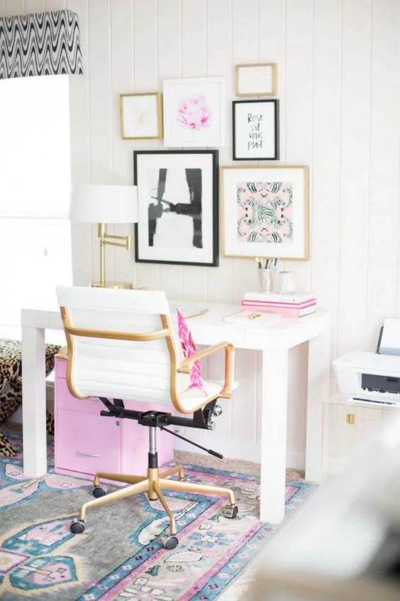 a modern home office with touches of pink   in the gallery wall, books, a pillow and a storage unit under the desk