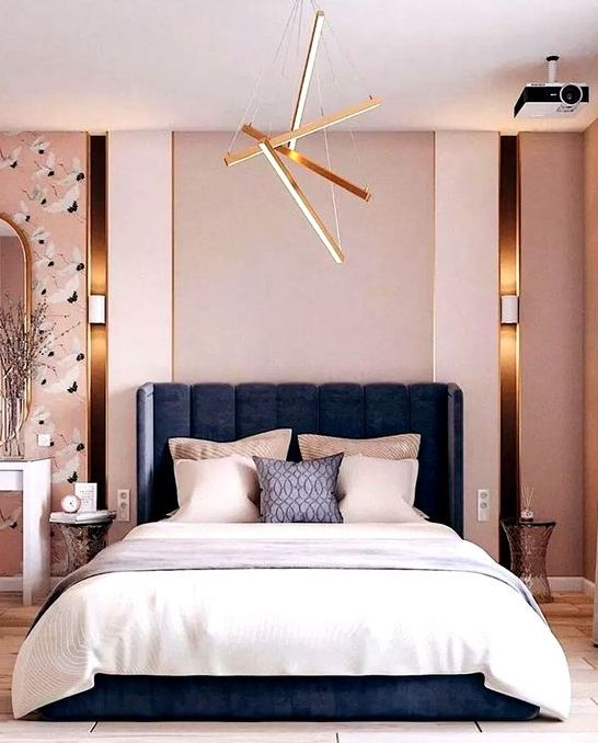 a modern luxurious bedroom with pink walls, catchy wallpaper, a navy bed, neutral bedding and touches of gold here and there