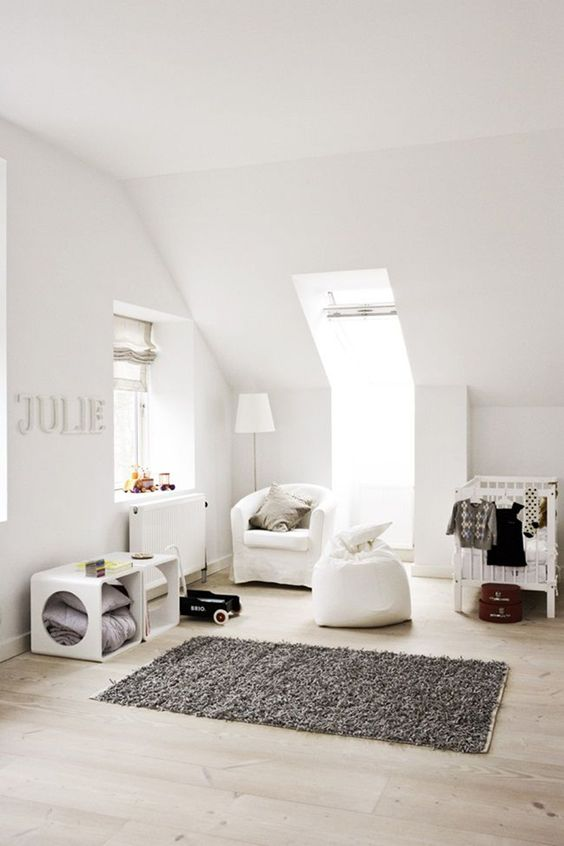 a modern neutral nursery with two windows, white furniture, a rug and lots of storage units for a littel kid