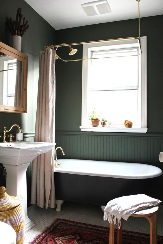 a moody vintage-inspired bathroom with hunter green walls and beadboard, a black tub, a tile floor and a free-standing sink plus touches of brass
