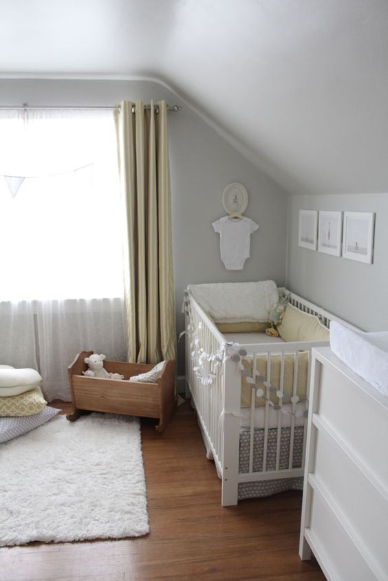 a neutral and peaceful nursery with dove grey walls, yellow curtains, grey and yellow bedding and a cute gallery wall