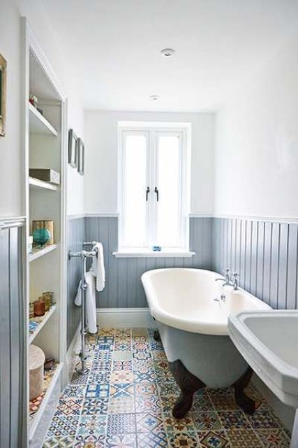 a neutral and welcoming bathroom with powder blue beadboard, printed tiles, a built-in storage unit and a blue tub