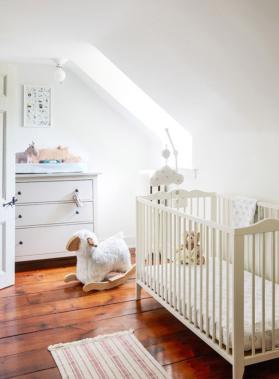 a neutral attic nursery with simple and casual furniture, muted and printed textiles plus lots of cute toys