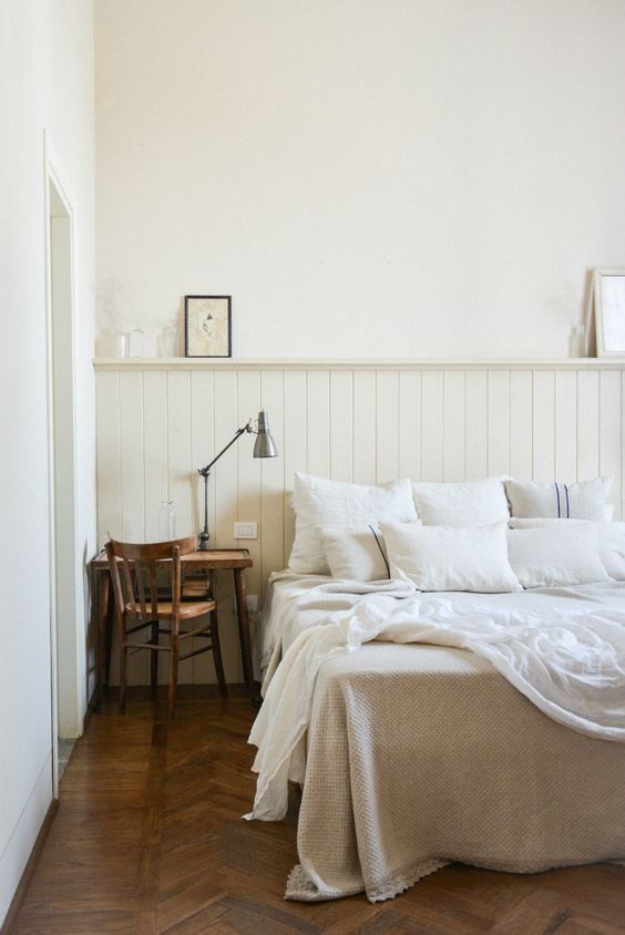 a neutral bedroom with neutral beadboard, a wooden desk and chair, some vintage touches here and there