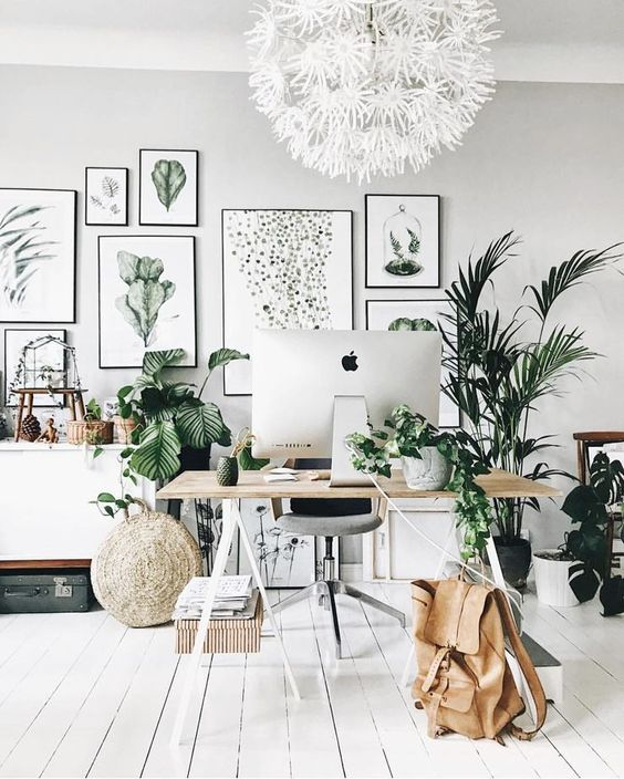 a neutral tropical home office with a large gallery wall, a white floral chandelier, lots of plants, a trestle desk and baskets