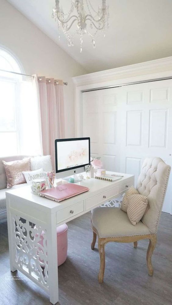 a neutral vintage inspired home office with pink curtains, pillows, an ottoman and even a laptop for a cute look