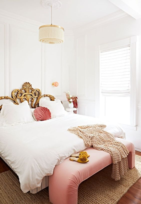 a refined bedroom in neutrals, with a gold exquisite bed, a pink bench and pillow plus a tassel chandelier