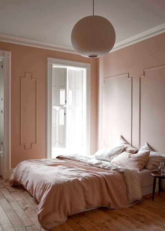 a refined vintage inspired bedorom with blush molding walls, blush and white bedding, a wooden floor and a paper lamp