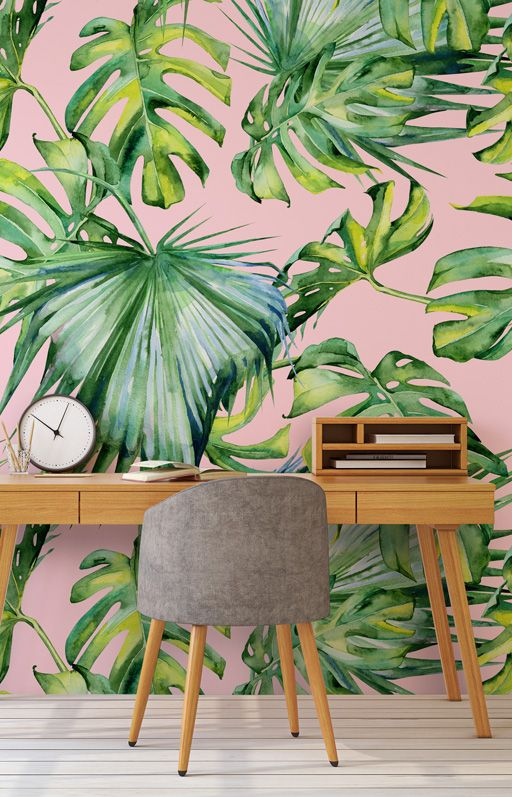 a simple tropical home office with an accent wall, a wooden desk, a grey chair and a clock is very chic