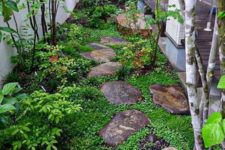 a small Japanese-inspired garden with rocks as pavements, greenery, shrubs and a couple of trees is very peaceful