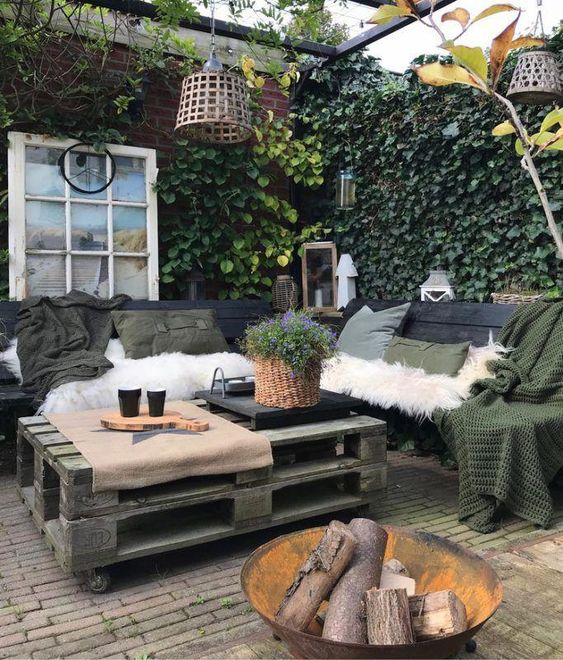 a small Nordic patio with pallet furniture, dark textiles, faux fur covers, pendant lamps, potted greenery and a fire pit