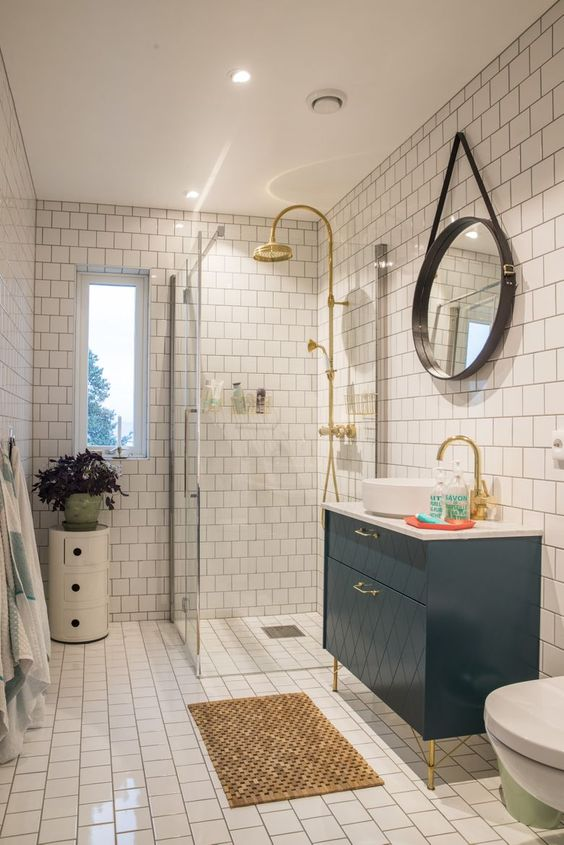 a small and bright bathroom with white tiles, a navy vanity, a side table with a plant and touches of gold here and there