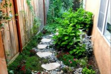 a small and bright garden nook with pebbles, greeneyr and bright blooms, shrubs and a climbing plants on the fence