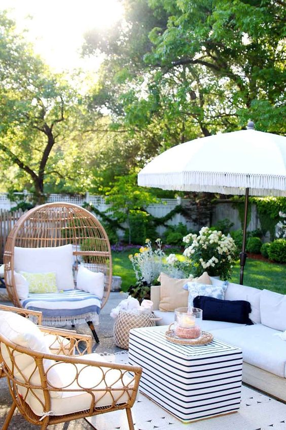 a small and cozy summer patio with neutral furniture, wicker chairs, printed textiles, baskets and a white umbrella over the space