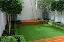 a small and elegant garden with a green lawn, with some flower beds with blooms and greenery and shrubs and trees