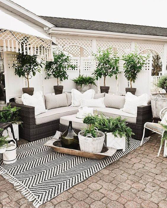 a small and elegant patio in a monochromatic color scheme, with a printed rug, a wicker sofa, potted greenery and some baskets