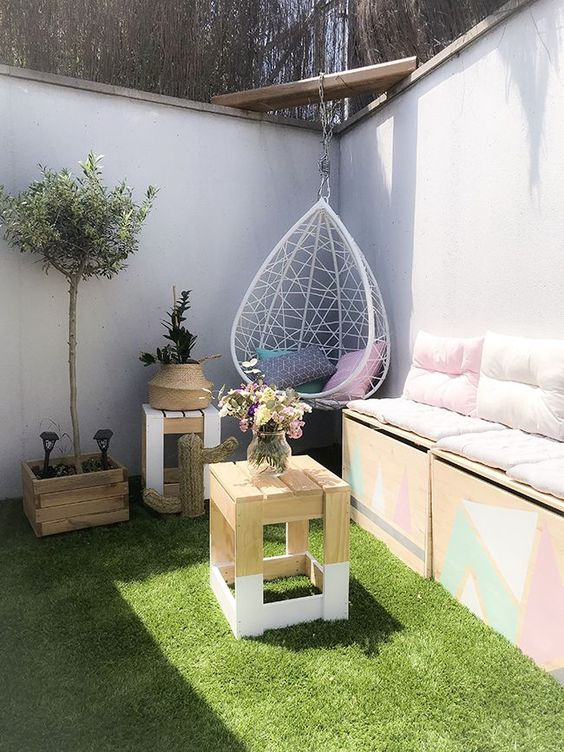 a small and fun pation with lawn, with a storage sofa, some side tables, potted greenery and a pendant egg chair