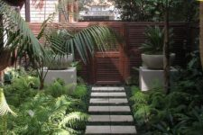 a small and lush tropical garden with lots of greenery, ferns and tropical plants in pots and on the ground