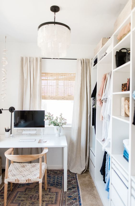 a small and neutral cloffice with a white makeshift closet, a white desk and woven chair, a paper lamp and a printed rug