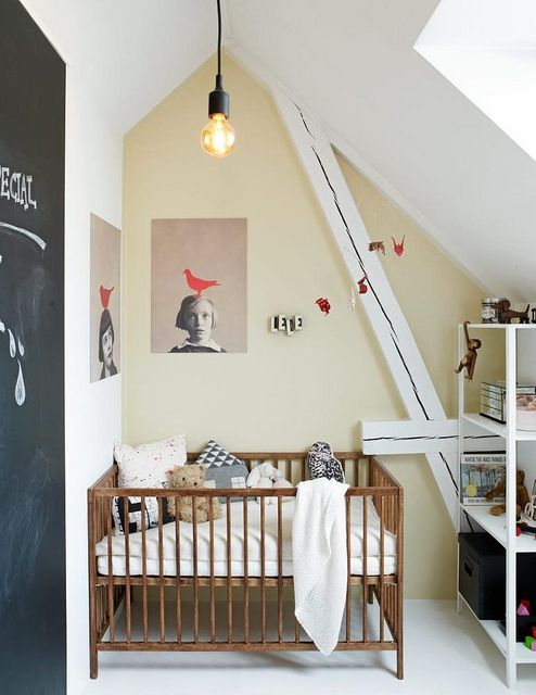 a small attic nursery with a catchy artwork, a chalkboard door, a simple crib and a storage unit for a modern look