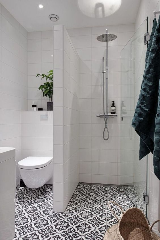 a small bathroom with a shower separate with white long tiles, a printed tile floor, a potted plant and a white vanity