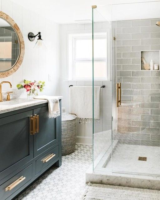 a small bathroom with grey long tiles and printed ones on the floor, a graphite grey vanity, touches of gold and a marble countertop