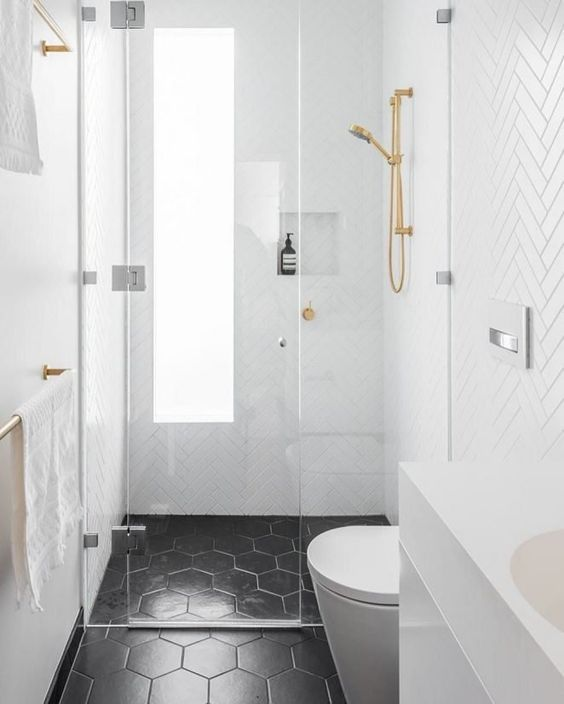 a small bathroom with white herringbone tiles and black hex ones, with a frosted glass window and gold fixtures