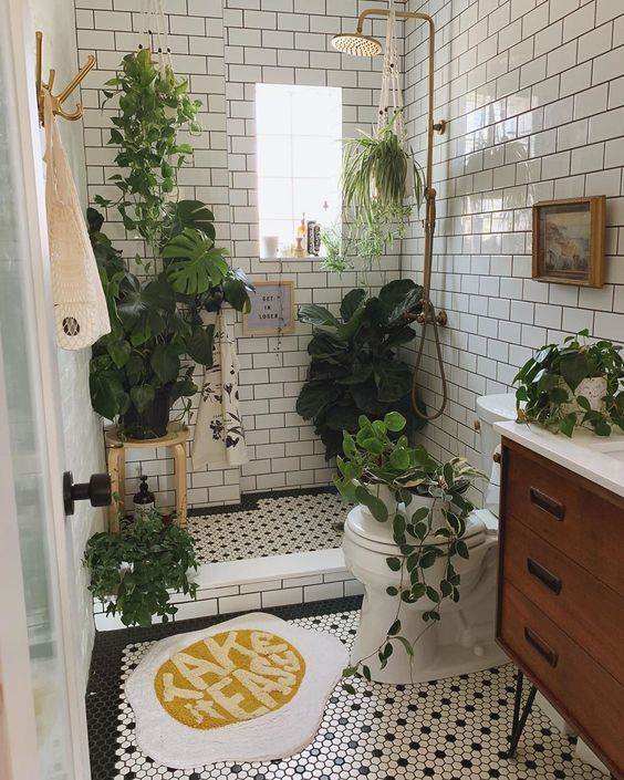 a small boho bathroom clad with white subway tiles, with black and white penny ones, with lots of plants for a forest feel