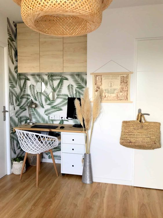a small boho tropical home office nook with a tropical wall, a white chair, pampas grass, a wicker lamp and an artwork