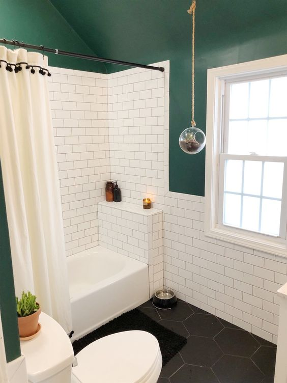 a small catchy bathroom with dark green walls and a ceiling, white subway tiles, black hex ones, a shower space and a window