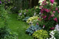a small colorful garden with a grene lawn, some shrubs, bright blooms, several trees in the corner