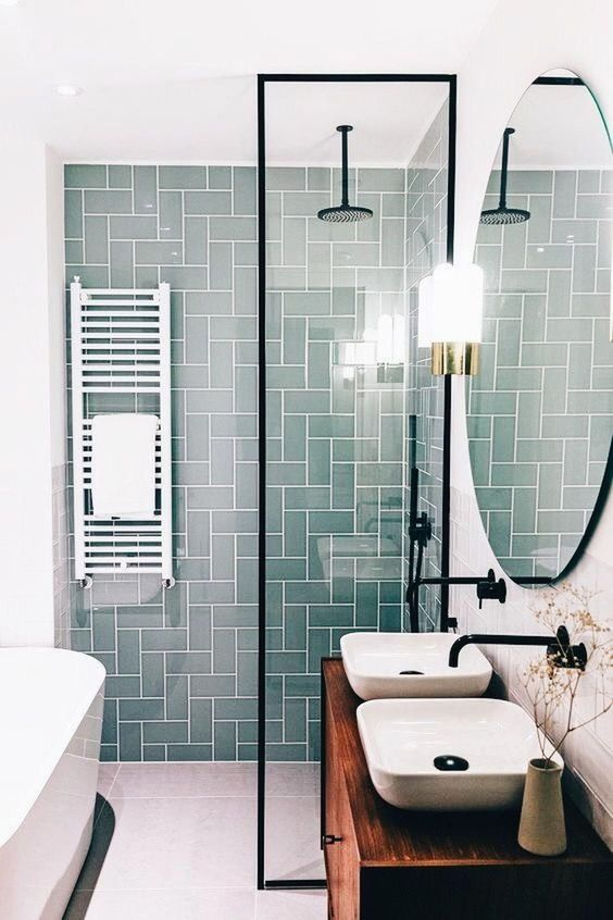 a small contemporary bathroom with a mint tile wall, a wooden vanity and touches of black for a modern feel