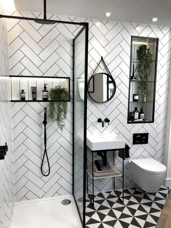 a small contemporary bathroom with herringbone clad tile walls, a printed floor, a small sink and a shower with a glass divider