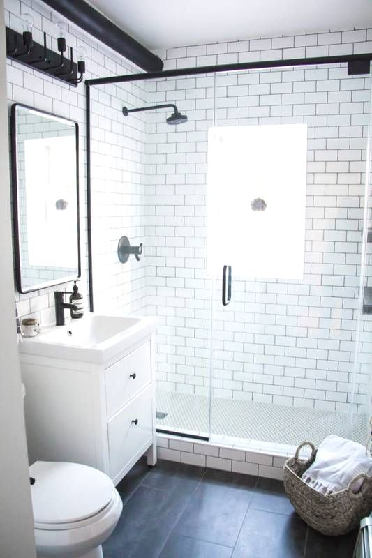 a small contemporary bathroom with white subway tiles, black tiles on the floor, a tiny vanity and black fixtures