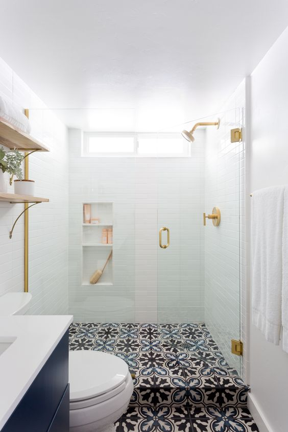 a small contemporary bathroom with white tiles in the shower, patterned tile floor, a navy vanity and touches of gold