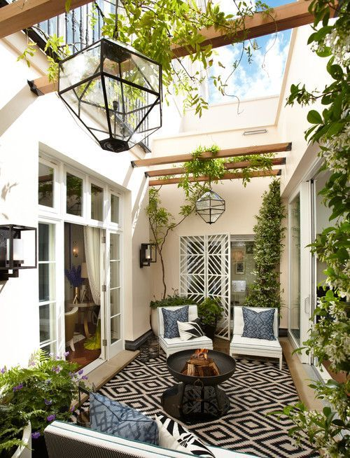 a small contemporary patio in a monochromatic color scheme, with a printed rug, blue pillows, lots of greenery, catchy lanterns and a fire pit