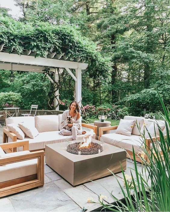 a small contemporary patio with simple neutral furniture, a large fire pit and some greenery and blooms around