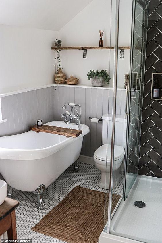 a small cute bathroom with grey beadboard, a black tile shower space, some wood tiles and potted greenery
