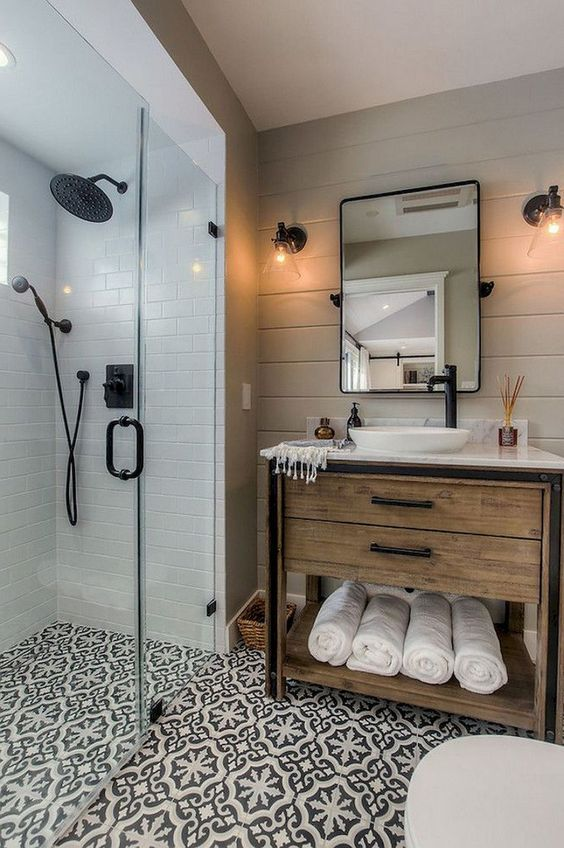 a small farmhouse bathroom with neutral tiles, patterned ones on the floor, a wooden vanity and black fixtures here and there