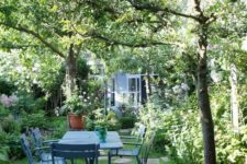 a small garden with a green lawn, some trees, lots of shrubs, trees and a blue garden dining set plus blooms