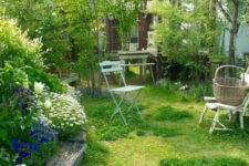 a small garden with a lawn, a flower bed with bright blooms, some vintage garden furniture and some shrubs and trees