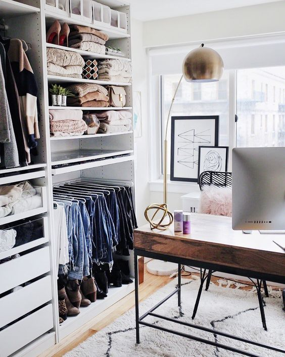 a small glam cloffice with a large makeshift closet, a stylish wood and metal desk, artworks and a catchy brass lamp