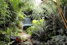 a small lush garden nook with lots of greenery, shrubs, some trees and tropical plants, a blue bench and a vase