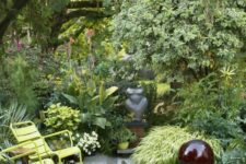 a small lush garden with lots of grasses, shrubs and flowers, some trees, a fire pit and garden chairs