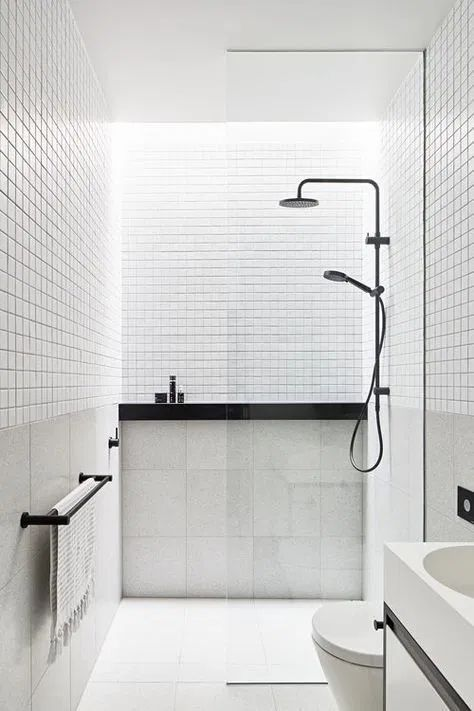 a small minimalist bathroom in black and white, with white small and large scale tiles, black fixtures and other touches