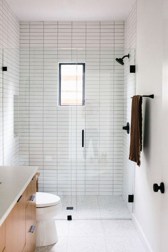 a small minimalist bathroom with neutral tiles, with skinny ones and printed ones on the floor, a small window and black fixtures for a modern feel