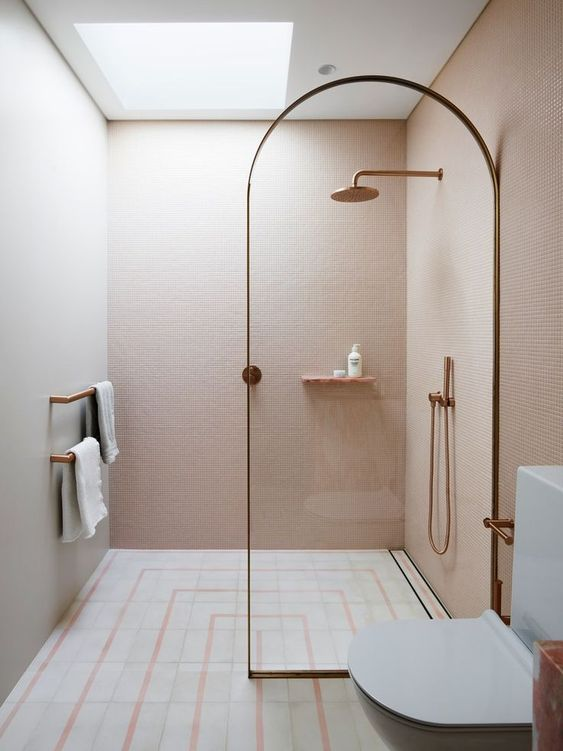 a small minimalist bathroom with pink walls, a printed tile floor, a glass divider and touches of rose gold