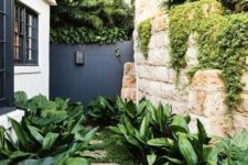a small modern garden nook with greenery, some lush tropical shrubs on both sides of the pavement