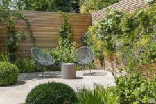 a small modern garden with lush grasses, some shrubs and some climbing greenery plus a whole living wall