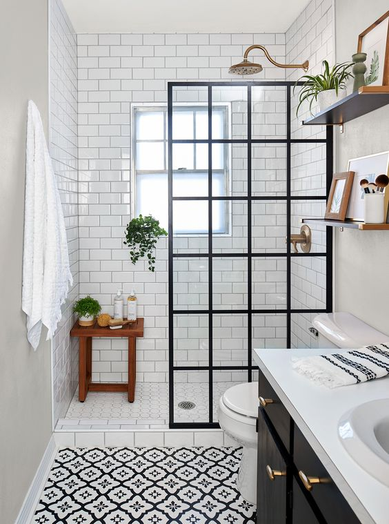 a small monochromatic bathroom clad with printed and white subway tiles, a black vanity, a black framed glass divider and brass touches
